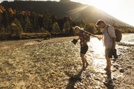 Austria, Alps, couple on a hiking trip wading in a brook - UUF16535