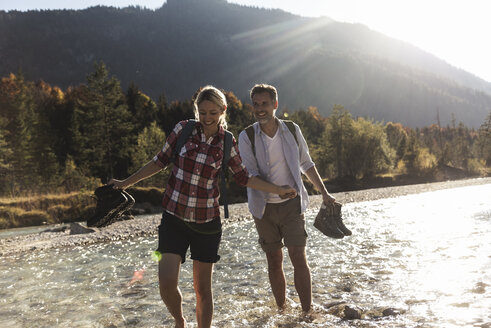 Austria, Alps, couple on a hiking trip wading in a brook - UUF16538