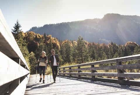 Austria, Alps, happy couple on a hiking trip crossing a bridge - UUF16550