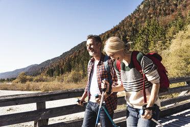 Austria, Alps, happy couple on a hiking trip crossing a bridge - UUF16553