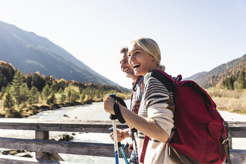 Austria, Alps, happy couple on a hiking trip crossing a bridge - UUF16556