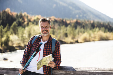 Austria, Alps, smiling man on a hiking trip with map on a bridge - UUF16562