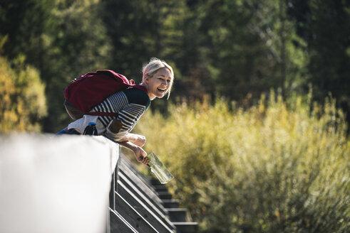 Austria, Alps, happy woman on a hiking trip with map on a bridge - UUF16565