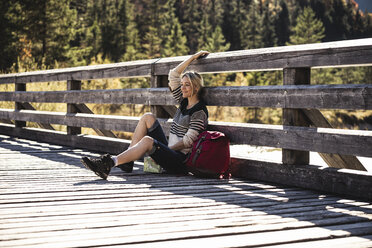 Austria, Alps, woman on a hiking having a break sitting on a bridge - UUF16568