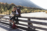 Austria, Alps, couple on a hiking trip having a break on a bridge - UUF16571