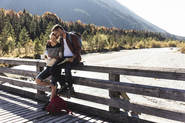Austria, Alps, couple on a hiking trip having a break on a bridge - UUF16571