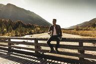 Austria, Alps, man on a hiking trip having a break on a bridge - UUF16574
