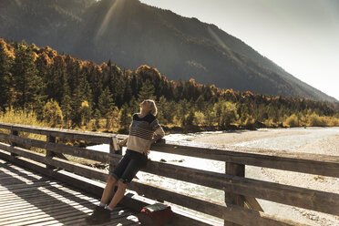 Austria, Alps, woman on a hiking trip having a break on a bridge - UUF16577