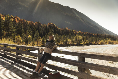 Austria, Alps, woman on a hiking trip having a break on a bridge - UUF16577