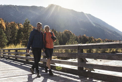 Austria, Alps, happy couple on a hiking trip crossing a bridge - UUF16580
