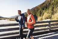 Austria, Alps, happy couple on a hiking trip crossing a bridge - UUF16583