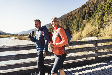 Austria, Alps, happy couple on a hiking trip crossing a bridge - UUF16583