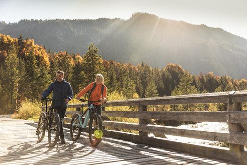 Austria, Alps, couple with mountain bikes crossing a bridge - UUF16592