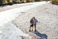Austria, Alps, couple on a hiking trip standing at a brook - UUF16598