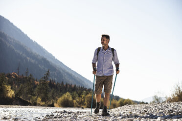 Austria, Alps, man on a hiking trip walking on pebbles along a brook - UUF16601