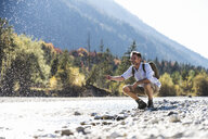 Austria, Alps, man on a hiking trip having a cooling break at a brook - UUF16604