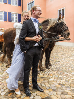 Happy bride and groom on cobblestone sqaure with carriage - LAF02220