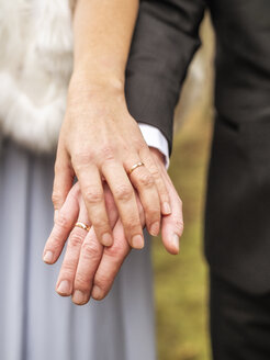 Close-up of bride and groom holding hands - LAF02223