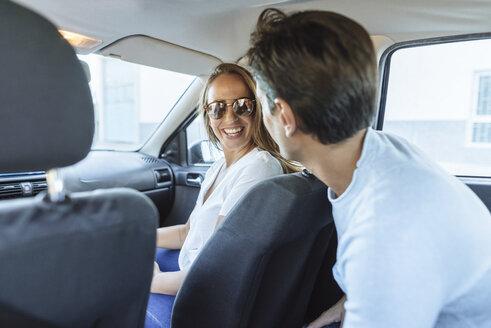 Spain, Andalusia, cadiz, El Puerto de Santa Maria, Woman in car front seat with man in the back. - KIJF02227