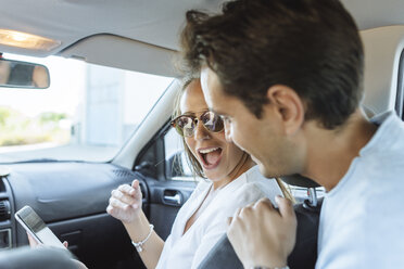 Happy couple in car with man on back seat and woman with cell phone on front passenger seat - KIJF02230