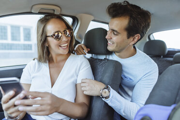 Happy couple in car with man on back seat and woman with cell phone on front passenger seat - KIJF02233