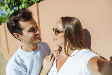 Selfie of a smiling couple looking at each other on a sunny day - KIJF02242