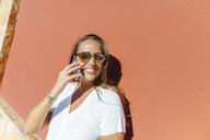 Smiling woman on cell phone on a sunny day - KIJF02251