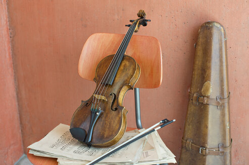 Violin, bow and sheet music on wooden chair with violin case in the background - CRF02815