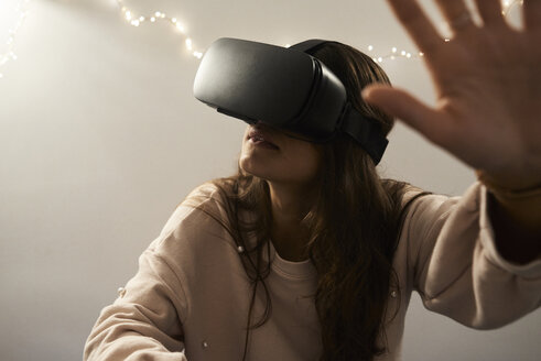 Young woman using virtual reality headsets playing games on the sofa at home at night. - IGGF00733
