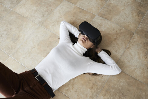 Overhead of millennial brunette female using virtual reality headsets lying on the floor at home. - IGGF00742