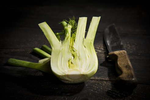 Sliced fennel and kitchen knife on dark wood - MAEF12773