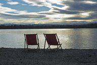 Germany, two empty deckchairs standing at lakeshore of Ammersee by sunset - CRF02822