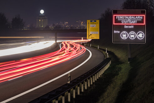 Germany, Stuttgart, Warning sign for particulate pollution alert and traffic at night - WDF05049