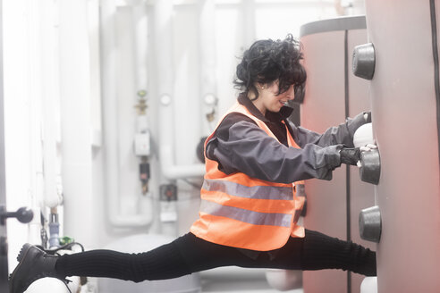 Technikerin macht Spagat im Heizungskeller - SGF02212