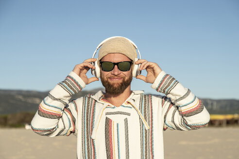 Man with headphones and sunglasses at the beach - KBF00466