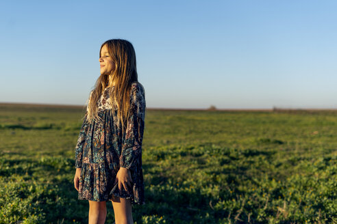 Smiling girl wearing dress with floral design standing in nature enjoying sunset - ERRF00665