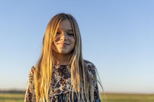 Portrait of smiling blond girl at sunset - ERRF00668