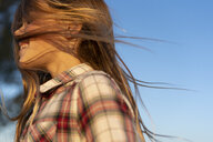 Profile of laughing girl with blowing hair against blue sky - ERRF00674