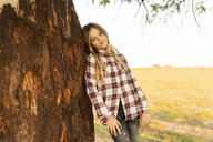 Portrait of blond girl leaning against tree trunk - ERRF00677