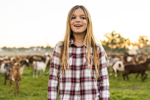 Portrait of smiling blond girl standing on pasture with goat herd in the background - ERRF00698