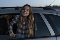 Portrait of smiling girl leaning out of car window in the evening - ERRF00725