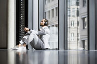 Casual business man with headphones leaning onto window in modern office space with closed eyes listening to podcast - SBOF01643