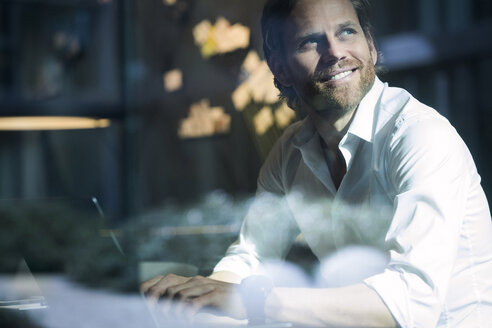 Smiling smart business man working on laptop in modern office space looking out of window - SBOF01652
