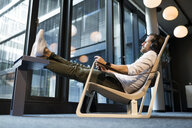 Casual businessman relaxing in lounge area of a coworking space, listening music - SBOF01655