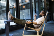 Casual businessman relaxing in lounge area of a coworking space - SBOF01658