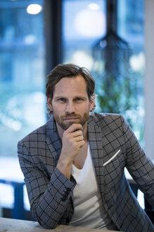 Portrait of confident smart entrepreneur in modern office lounge - SBOF01676