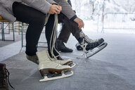 Couple sitting on bench at the ice rink, putting on ice skates - ZEDF01828