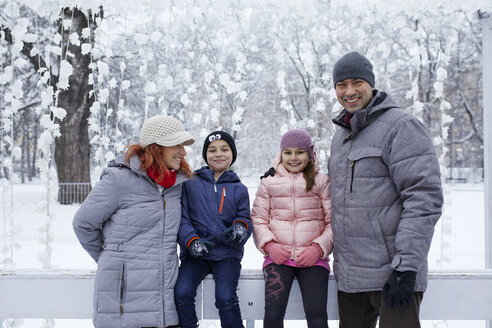 Family with two kids on the ice rink, portrait - ZEDF01831