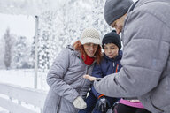 Family with two kids on the ice rink, looking at selfies on their smartphone - ZEDF01834