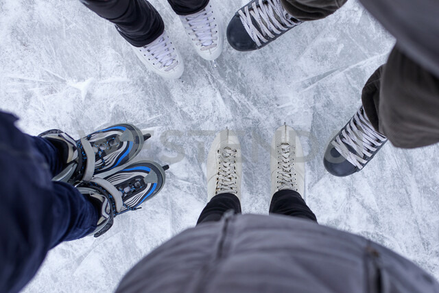 Family with two kids standing on the ice rink, close up of shoes - ZEDF01837